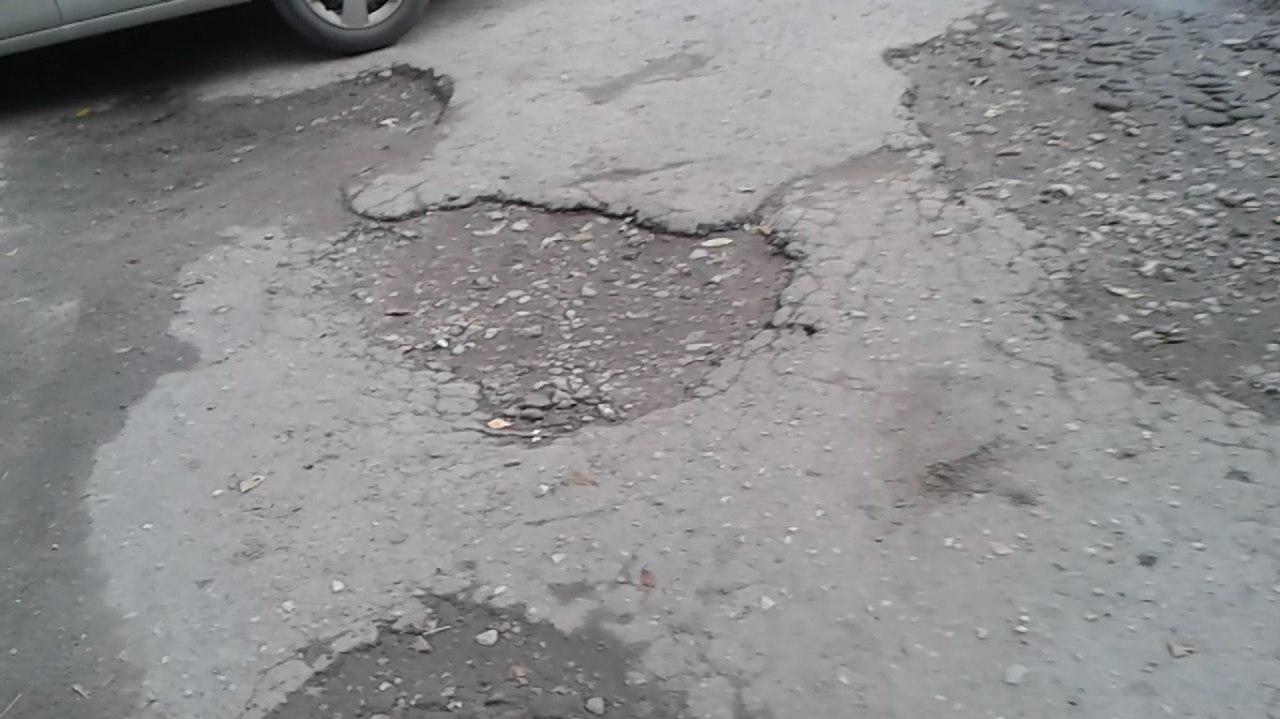 Во двор не проехать - дорога на улице Новаторов усеяна глубокими ямами